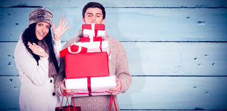 Composite image of young couple with many christmas presents Stock Image