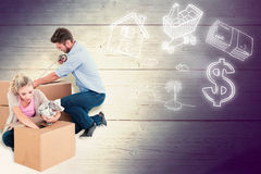 Composite image of young couple packing moving boxes Stock Image