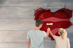 Composite image of young couple painting with roller Royalty Free Stock Image