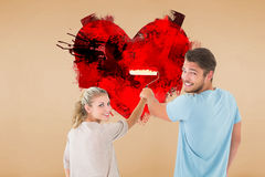 Composite image of young couple painting with roller Royalty Free Stock Photography