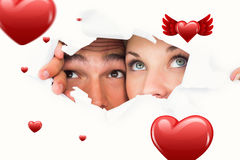 Composite image of young couple peeking through torn paper. Young couple peeking through torn paper against hearts royalty free stock photo