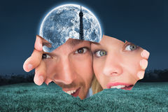 Composite image of young couple peeking through torn paper Royalty Free Stock Photos