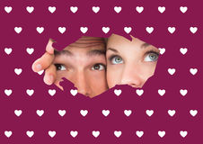 Composite image of young couple peeking through torn paper. Young couple peeking through torn paper against valentines day pattern stock photo