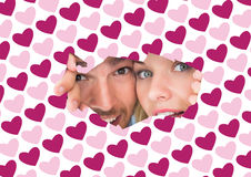 Composite image of young couple peeking through torn paper. Young couple peeking through torn paper against valentines day pattern stock image