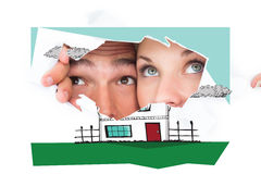 Composite image of young couple peeking through torn paper Royalty Free Stock Images