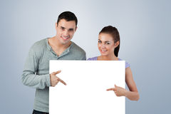 Composite image of young couple pointing at banner in front of them Stock Images