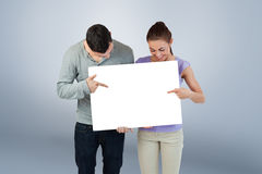 Composite image of young couple pointing at banner they are holding Stock Photos