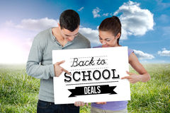 Composite image of young couple pointing at banner they are presenting Royalty Free Stock Photos