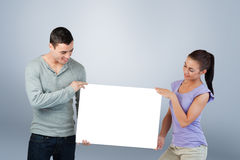 Composite image of young couple presenting banner together Royalty Free Stock Images