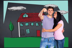 Composite image of young couple showing keys to house Royalty Free Stock Photo