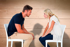 Composite image of young couple sitting in chairs arguing Stock Photography