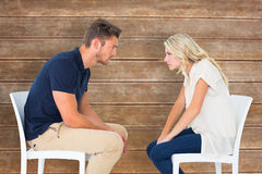 Composite image of young couple sitting in chairs arguing Stock Photos