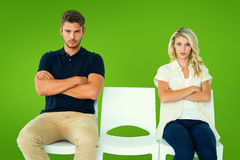 Composite image of young couple sitting in chairs not talking during argument Royalty Free Stock Image