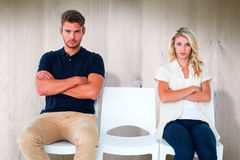 Composite image of young couple sitting in chairs not talking during argument Royalty Free Stock Photos