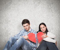 Composite image of young couple sitting on floor with broken heart Royalty Free Stock Photography