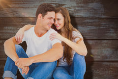 Composite image of young couple sitting on floor embracing Stock Image