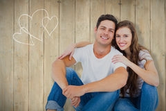 Composite image of young couple sitting on floor hugging Stock Image