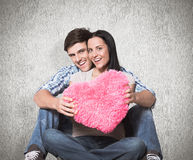 Composite image of young couple sitting on floor smiling Royalty Free Stock Images