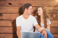 Composite image of young couple sitting on floor using laptop Stock Photo