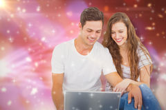 Composite image of young couple sitting on floor using laptop Royalty Free Stock Image