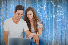 Composite image of young couple sitting on floor using laptop Royalty Free Stock Photography