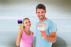 Composite image of young couple smiling and holding paintbrushes Stock Images