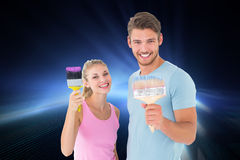 Composite image of young couple smiling and holding paintbrushes Stock Image