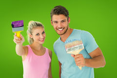 Composite image of young couple smiling and holding paintbrushes Stock Photo