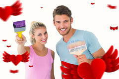 Composite image of young couple smiling and holding paintbrushes. Young couple smiling and holding paintbrushes against hearts stock photo