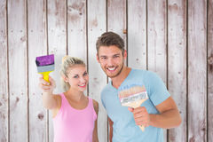 Composite image of young couple smiling and holding paintbrushes Royalty Free Stock Photography