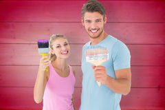 Composite image of young couple smiling and holding paintbrushes Royalty Free Stock Photo