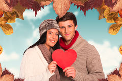 Composite image of young couple smiling holding red heart Royalty Free Stock Photo