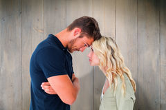 Composite image of young couple standing head to head Royalty Free Stock Photography