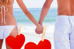 Composite image of young couple in swimwear holding hands Royalty Free Stock Photos