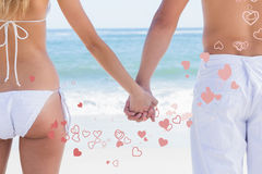 Composite image of young couple in swimwear holding hands. Young couple in swimwear holding hands against valentines heart design stock photo