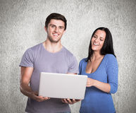 Composite image of young couple using a laptop Royalty Free Stock Images