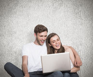 Composite image of young couple using laptop on floor Royalty Free Stock Photo