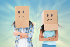 Composite image of young couple wearing sad face boxes over head Royalty Free Stock Photos