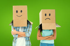 Composite image of young couple wearing sad face boxes over head Stock Photos