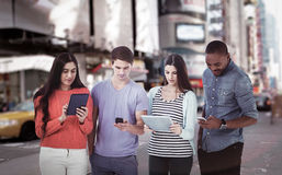 Composite image of young creative team looking at phones and tablets. Young creative team looking at phones and tablets against blurry new york street royalty free stock photos
