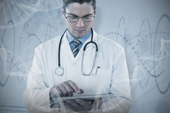 Composite image of young doctor using digital tablet. Young doctor using digital tablet against red spiral dna pattern on screen Royalty Free Stock Photo
