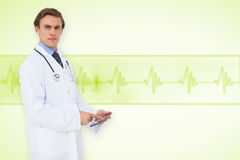 Composite image of young doctor using tablet pc Stock Photography