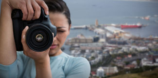Composite image of young female photographer photographing through digital camera. Young female photographer photographing through digital camera against view of Royalty Free Stock Photos