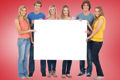 Composite image of young friends showing card Stock Image