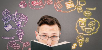 Composite image of young geek looking over black book Royalty Free Stock Photo