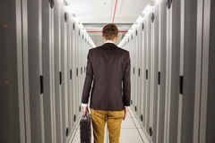 Composite image of young geeky businessman holding briefcase Royalty Free Stock Images