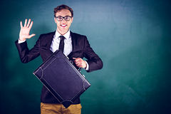Composite image of young geeky businessman holding briefcase Stock Photo