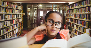 Composite image of young girl day dreaming by book at table Royalty Free Stock Photos