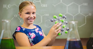 Composite image of young girl smiling while holding molecular structure Stock Image