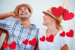 Composite image of young hip couple laughing on bench Stock Photos